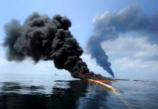 Dark clouds of smoke and fire emerge as oil burns during a controlled fire in the Gulf of Mexico, May 6, 2010. The U.S. Coast Guard, working with BP, local residents and other federal agencies, conducted the burn to help prevent the spread of oil followin